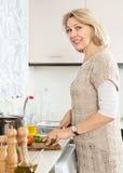 Hausfrau, die das veggy Mittagessen cuting ist Lizenzfreie Stockbilder