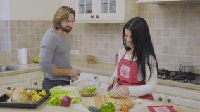 Hausfrau, die den Salat und die Gespräche mit ihrem Ehemann an der Küche vorbereitet stock video footage