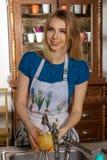 Hausfrau, die in der Küche lächelt Stockfotos