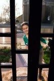 Hausfrau, die durch Glastür schaut Lizenzfreie Stockfotos