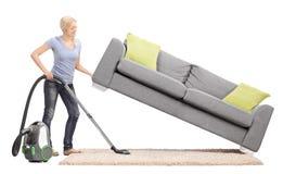 Hausfrau, die ein Sofa anhebt und unter es Staub saugt Stockbild