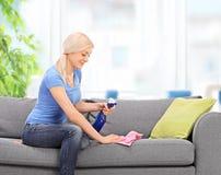 Hausfrau, die eine Couch mit einem Lappen säubert Lizenzfreie Stockfotos