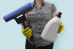 Hausfrau, die einen Mopp und ein flüssiges Reinigungsmittel hält Lizenzfreies Stockbild