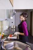 Hausfrau, die einen roten Pfeffer schneidet Lizenzfreie Stockbilder