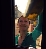Hausfrau, die Fenster abwischt Stockbild
