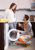 Hausfrau, die gebrochene Waschmaschine zeigt Lizenzfreies Stockbild