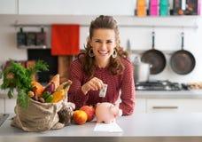 Hausfrau, die Geld in Sparschwein steckt Lizenzfreie Stockbilder