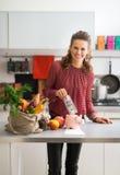 Hausfrau, die Geld in Sparschwein steckt Lizenzfreie Stockfotos