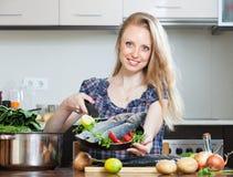 Hausfrau, die lubina Fische in der Küche kocht Stockfotografie
