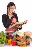 Hausfrau, die mit einem Buchrezept denkt Stockfotos