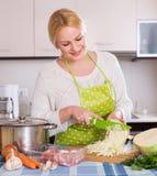 Hausfrau, die mit Fleisch und Kohl kocht Stockbild