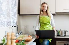 Hausfrau, die mit Notizbuch in der Küche kocht Lizenzfreie Stockbilder