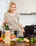 Hausfrau, die Notizbuch beim Kochen des Gemüses verwendet Stockfotos