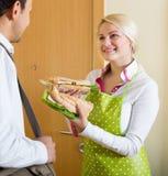Hausfrau, die Sandwich für Ehemann zubereitet Lizenzfreie Stockbilder