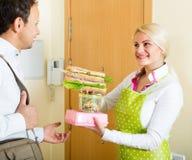 Hausfrau, die Sandwich für Ehemann zubereitet Stockbilder