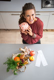 Hausfrau, die Sparschwein nach dem Einkauf zeigt Stockfotos