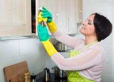 Hausfrau, die Stellen von den Schränken in der Küche entfernt Stockfoto