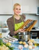 Hausfrau, die Suppe mit Fischen kocht Stockbild