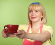 Hausfrau, die Tee in der roten Schutzkappe erhält Stockfotografie