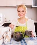 Hausfrau, die Tee und das Lächeln macht Stockbild
