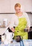 Hausfrau, die Tee und das Lächeln macht Lizenzfreie Stockbilder