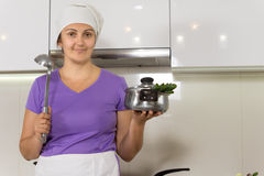 Hausfrau, die Topf zeigend steht stockfoto