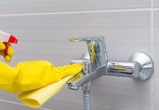 Hausfrau, die unter der Dusche den Hahn abputzt Lizenzfreies Stockfoto