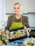 Hausfrau, die zu Hause Fische kocht Lizenzfreie Stockfotografie