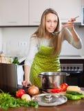 Hausfrau im Schutzblech Suppe mit Notizbuch kochend Lizenzfreies Stockbild