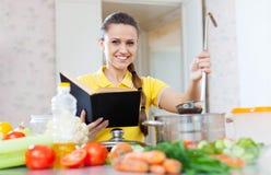 Hausfrau liest Kochbuch für Rezept Stockbilder