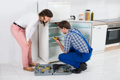 Hausfrau Looking At Worker, das Kühlschrank repariert Stockfoto