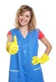 Hausfrau mit dem blonden Haar, das sich Daumen zeigt Stockfotos