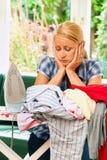 Hausfrau mit Eisen während des Bügelns und der Wäscherei. Stockbild