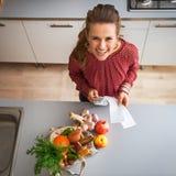 Hausfrau mit Geld- und Einkaufkontrollen achtern Stockbilder