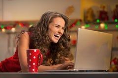 Hausfrau mit Schale heißer Schokolade unter Verwendung des Laptops Stockfotografie