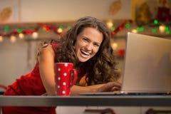 Hausfrau mit Schale heißer Schokolade unter Verwendung des Laptops Stockfoto
