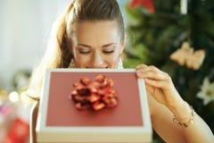 Hausfrau nahe dem Weihnachtsbaum, der innerhalb des Weihnachtsgeschenks schaut stockbilder