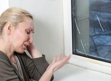 Hausfrau schreit, schlechtes Qualitätsfenster hat geborsten wegen des kühlen Wetters Lizenzfreie Stockfotografie