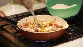 Hausfrau setzt Huhn und Rindfleisch in eine Wanne mit Gemüse für das Kochen des Pilafs ein stock video