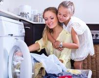 Hausfrau und Mädchen, die Wäscherei tun Stockbild