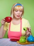 Hausfrau zu Hause mit einem roten Cup Lizenzfreies Stockbild