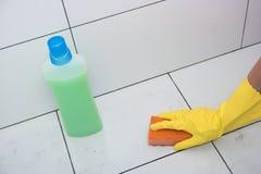 Hausfrauhand in einem gelben Gummihandschuh mit Schwamm Lizenzfreie Stockfotos
