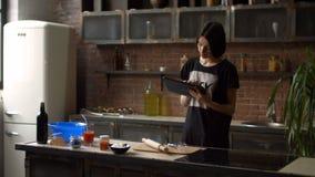 Hausfrauleserezept auf Tablette in der Küche stock footage