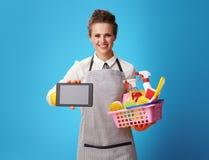 Hausgehilfin mit Korb mit den Reinigungsmitteln, die Tablet-PC zeigen lizenzfreies stockbild