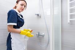 Haushälterin, die das Innere einer Dusche säubert Stockfotos
