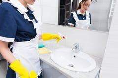 Haushälterin, die ein Handbecken sprüht Stockbild