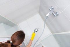 Haushälterin, die hinunter Duschkabine sprüht Stockfotos
