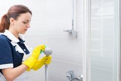 Haushälterin, die hinunter Duschkopf sich scheuert Stockfotos
