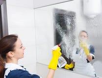 Haushälterin in einem Hotel ein Badezimmer instandhalten Lizenzfreie Stockfotografie