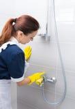 Haushälterin, welche die Installationen in einer Dusche säubert Stockbild